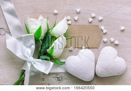 Valentine's Day bouquet of white roses with ribbon two gingerbread glaze scattered heart on a wooden table