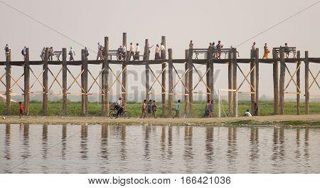 People Walking On The Ubein Bridge At Sunset