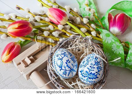 Traditional Czech easter decoration - regional wooden ratchet instrument with painted blue eggs in wicker nest with pussycats and tulips flower. Spring easter holiday arrangement.