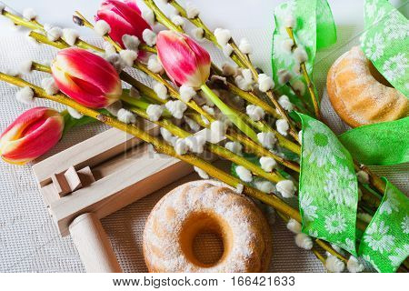 Traditional Czech easter decoration - regional wooden ratchet instrument with homemade cake with pussycats and tulips flower. Spring easter holiday arrangement.
