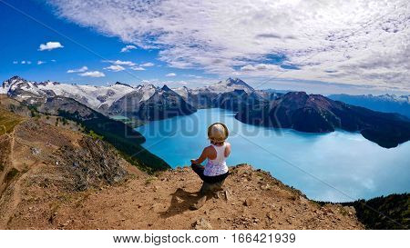 Inner Peace. Woman meditating abover alpine lake. Panorama Ridge. Garibaldi Lake. Garibaldi Provincial Park. Whistler. British Columbia. Canada.