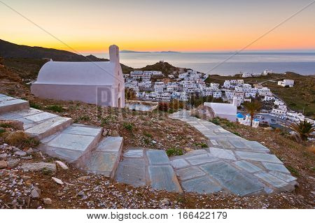 View of Chora on Ios island early in the morning. Santorini island can be seen on the horizon.