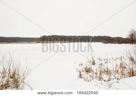 Winter River Covered With Snow With A Forest On The Far Shore