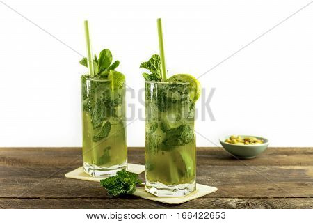 A photo of mojito cocktails with mint leaves, wedges of lime, drinking straws and a snack, with copy space. Selective focus