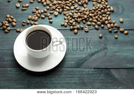 A cup of black coffee on a wooden boards texture, with beans scattered around, with copy space. A horizontal design template for a cafe or shop