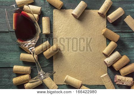 A piece of old parchment paper with a frame of corks and a glass of red wine on a dark background. A retro-styled wine tasting invitation, horizontal design template