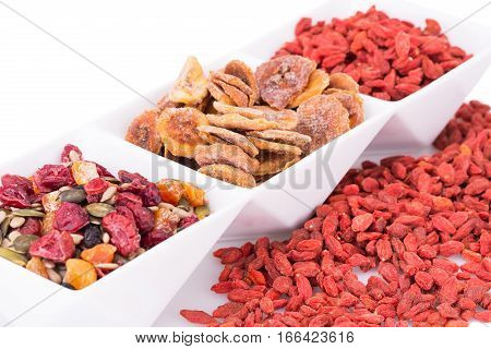 Dried fruits berries and seeds in bowl on white background.