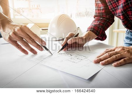 Architects engineer discussing at the table with blueprint - Closeup on hands and project print