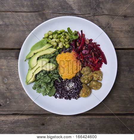 Nourish Bowl with Edamame Black Rice Avocado Spinach kale carrot cashews and beetroot on a Rustic wood background