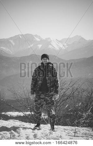 middle-aged male traveler on a background of mountains in the winter a black and white photo