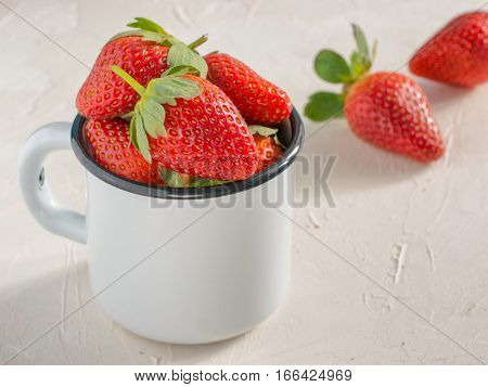 Fresh red strawberries in metal cup. Strawberry in rustic cup on oriental white background