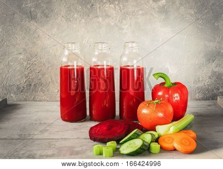 Fresh juice from vegetables tomato pepper celery carrots cucumber beets poured into small glass bottles which stand side by side on grey wooden table. Horizontal arrangement front view. Place for text