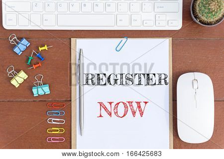 Text Register now on white paper which has keyboard mouse pen and office equipment on wood background / business concept.