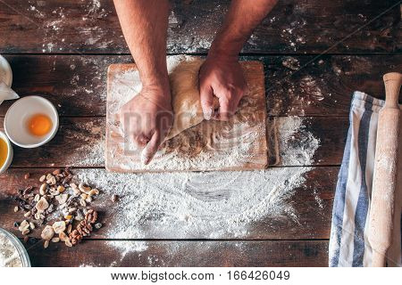 Hands kneading raw dough on table flat lay. Top view on baker workplace, working with pastry, free space on flowered table. Culinary, cooking, bakery concept