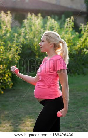 Side view on pregnant woman with dumbbells. Young pretty expectant female doing fitness exercises outdoor, green nature background. Sport, workout, healthy pregnancy concept
