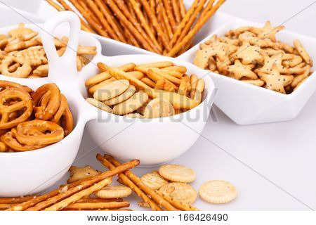 Different salted crackers in bowls on white background.