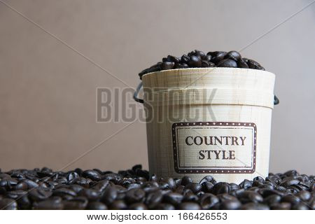 Coffee beans with casks on wood background