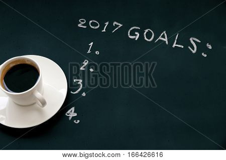 2017 goals list with on blackboard and cup of coffee.