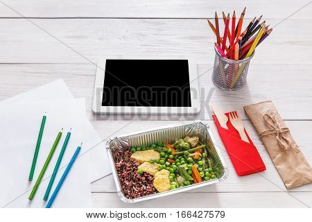 Healthy lunch and diet concept. Take away food in foil box, tablet with copy space and pencils on table of creative person, designer or school student. Meat with vegetables, POV on white wood