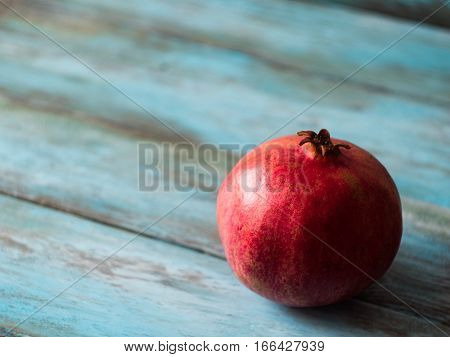 Pomegranate fruit on old table, side view.