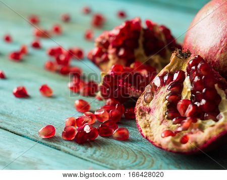 Heart made of pomegranate seeds on old wooden table, side view