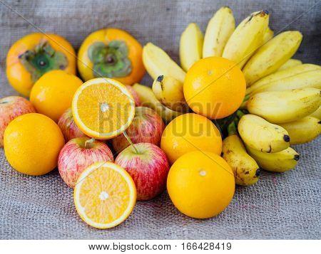 fruits apples oranges banana plums on brown hemp sack texture background