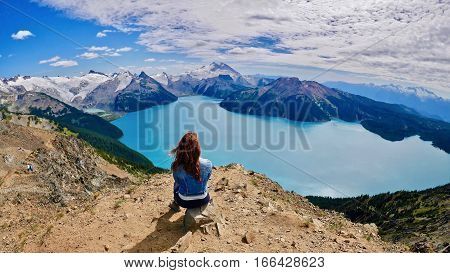 Inner Peace. Young woman meditating abover alpine lake and mountains. Panorama Ridge. Garibaldi Lake. Garibaldi Provincial Park. Whistler.  Squamish. Vancouver. British Columbia. Canada.