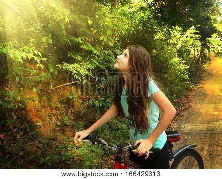 teen girl cycling through vietnam jungle hill close up photo