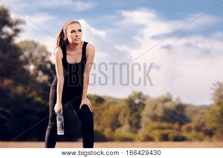 Fitness Girl with Water Bottle Hydrating after Outdoor Workout