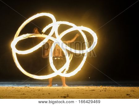 Long exposure shot of spinning burning torches in night fire show with vague silhouette of fakir man performing
