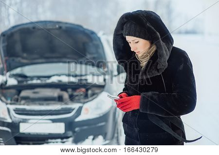 Beautiful girl in a fur coat is calling on the phone near the broken car