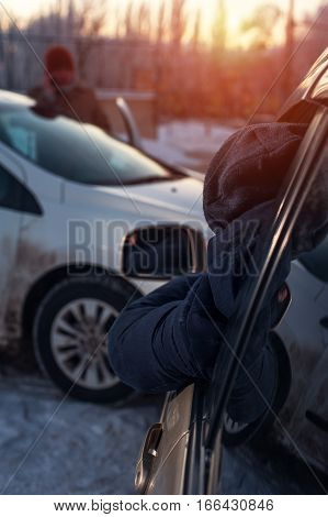 Male driver sitting in car and looking on damaged auto while another man calling to car assistance service. Auto crash. Shallow depth of field.