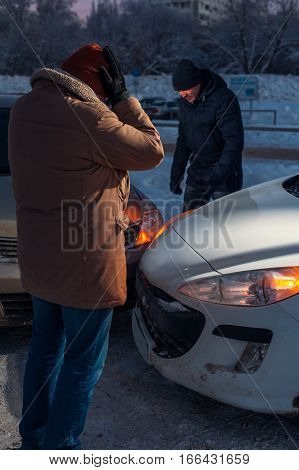 Two depressed drivers after car crash on winter city street.