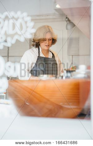 Portrait of adult blonde confectioner working in cafe from behind window. Focus on the face
