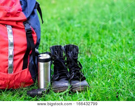 Hiking travel gear on glasses. Items include hiking boots cup mapbinoculars. Flat lay of outdoor travel equipment items for mountain camping trip. Greenery tone 2017