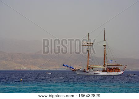 Walking on a wooden boat in the Red sea, Israel, with their sails, and mountains in the background.