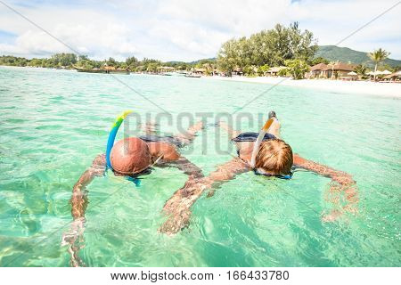 Senior couple vacationer swimming together on tropical Koh Lipe sea in Thailand - Snorkeling tour in exotic scenario - Active elderly and travel concept around world - Warm turquoise filter color tone
