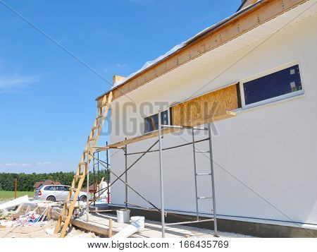 Facade building install windows, plastering, insulation, painting, stucco facade, install soffits and roofing. House Construction.