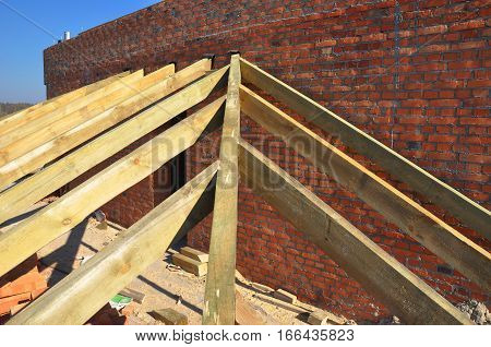 Roofing Construction. Close up on wooden rafters eaves wooden beams installed on brick wall with bitumen waterproofing membrane and metal anchors attachment.