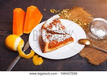 Pumpkin pie with powdered sugar on the kitchen table
