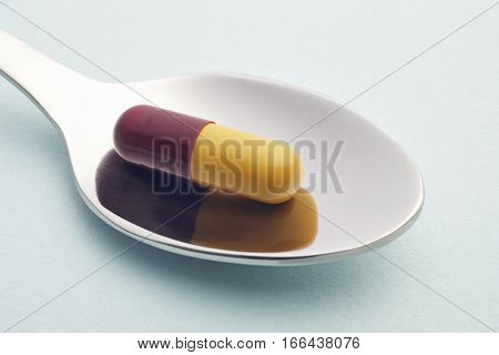 Pills and spoon detail. Blue background. Medicament treatment. Health care photo