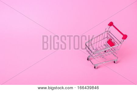 Empty shopping cart with the red handle on a pink background