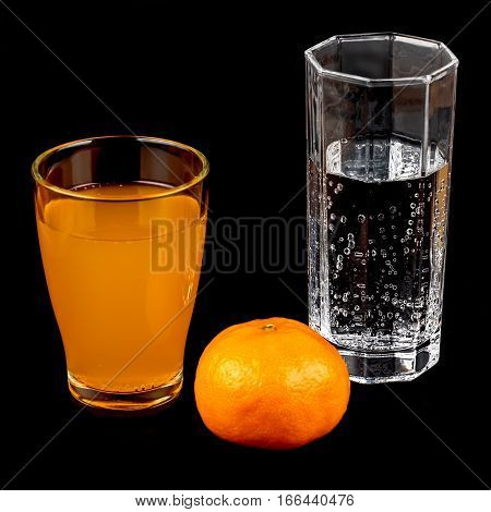 Tangerine and glass of mineral water and a glass of juice on a black background close-up.