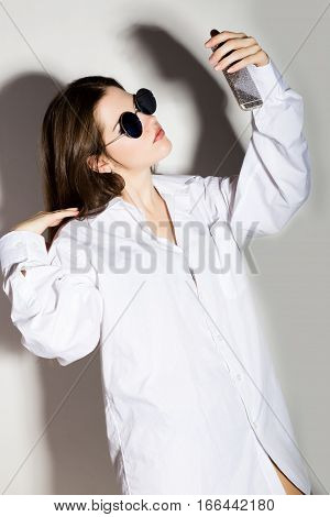 girl in a man's white shirt and sunglasses, holding phone, doing selfie