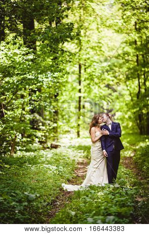 Groom and bride kissing in the spring forest