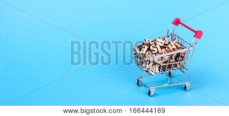 Shopping basket with letters of the alphabet made of wood on a blue background
