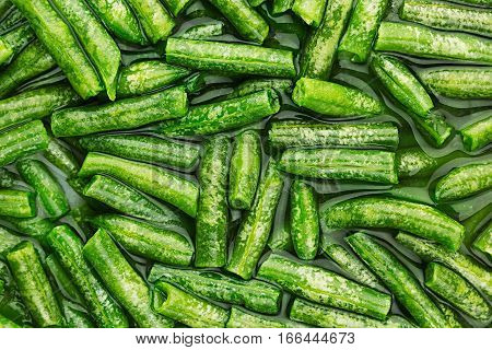 Wet fresh french green beans in water closeup as background. Healthy vitamin food.