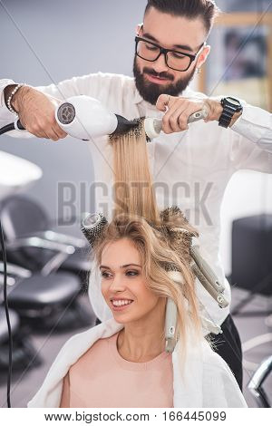 Calm professional stylist is combing woman hair. He is using expensive tools