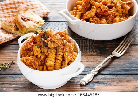 Fusilli pasta with chicken. Cooked in spicy sauce from tomatoes onion garlic dried oregano and thyme paprika and olive oil. Fresh bread white bowl and casserole on wooden brown rustic table.