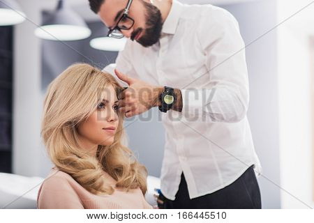 Calm lady is sitting in a chair while stylist is making her hairstyle